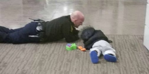 Find out why this photo of a police officer playing with a toddler goes viral