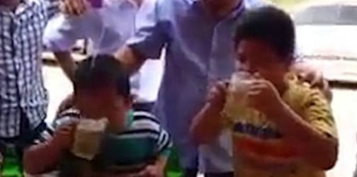 Two boys participate in a beer drinking competition while adults cheer
