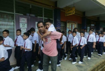 Father carries his disabled son to school on his first day