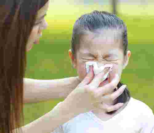 chinese mum helping daughter blow her nose