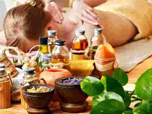 woman getting relaxing massage with luxury oils and herbs