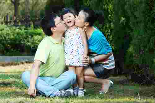 Chinese mum and dad kissing daughter