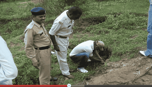 A still, police officers digging up the baby.