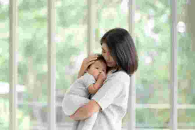 postpartum doula provides support to mother & her family