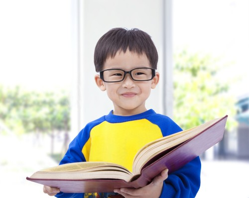 Malay kid with glasses reading a book