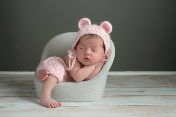A two week old newborn baby girl sleeping in a little chair. She is wearing a crocheted, pink bear bonnet and matching shorts. Shot in the studio on a gray background.