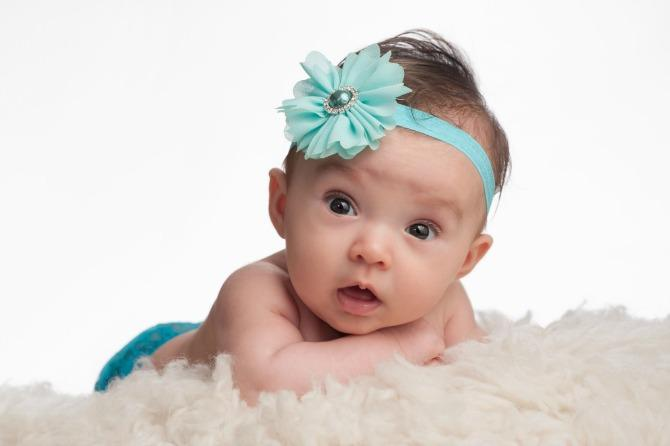 A portrait of an alert, 3 month old baby girl wearing a turquoise blue flower headband. She is lying on her tummy, propped up on her forearms on a cream colored sheepskin rug.