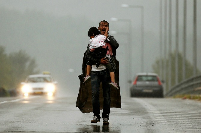 A man and his child wander aimlessly in search of shelter