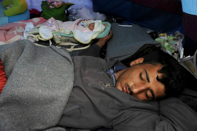 Syrian refugee Saad sleeps next to his 10-day-old daughter, Yasmine, who was born while on the refugee trail in Greece.