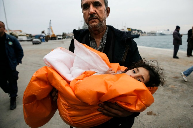 A Syrian refugee arriving in Greece carries his daughter covered with a blanket, after being rescued at open sea.
