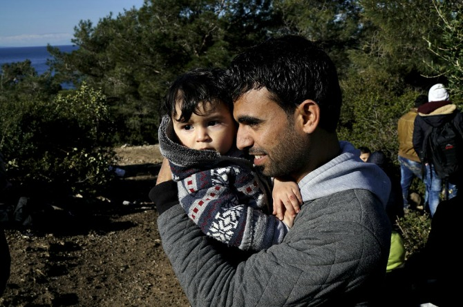 A Syrian refugee holds his infant as he waits near a beach in Dikili, Turkey, after Turkish gendarmes prevented them from sailing off for Greece.