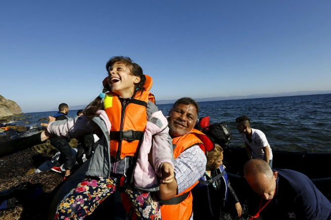 A Syrian refugee girl is joyously lifted by her father after arriving to a beach on the Greek island of Lesbos following a long journey at sea.