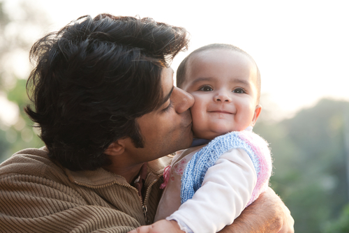 Father kissing baby's cheeks