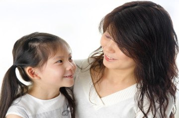 Asian mother and her daughter having conversation in home