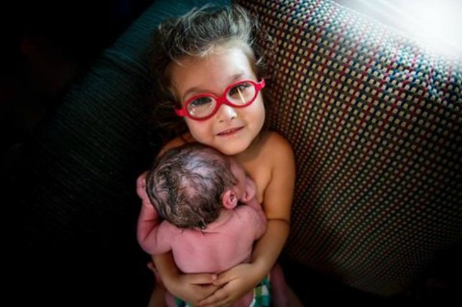 girl helps deliver her brother
