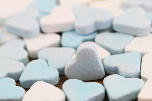 Blue and white sugar hearts spread out on flat surface