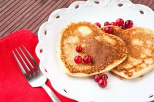 Heart shaped pancakes with cranberries on white porcelain plate. Celebration morning dessert. Indoors closeup.