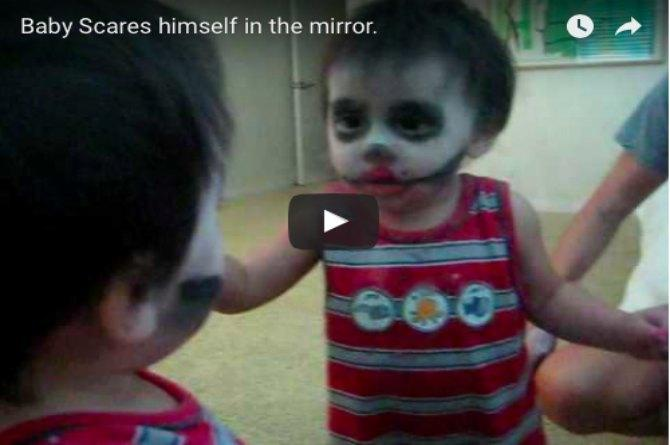 Baby looks in the mirror and is scared by what he sees