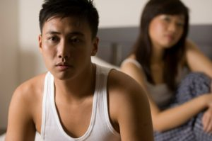An asian man looks unhappy sitting on the bed, with his partner (out of focus) behind him